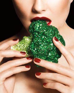 A beautiful shirtless woman bites into raw broccoli that's encrusted with glitter and rhinestones.