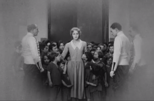 A crowd of Orphans being kept out of a private gentleman's club, while a Young Woman is fallen in love with