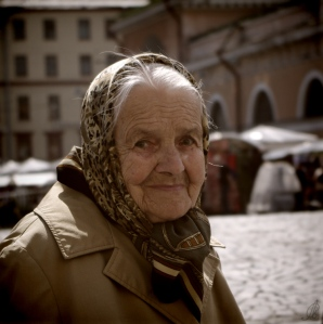 An old woman with a head scarf, smiling slightly. A wisp of hair escapes her scarf.