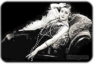 An elderly flapper who is swooning on a chaise longue